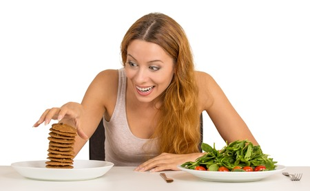 obsessed: Portrait young woman deciding whether to eat healthy food or sweet cookies she is craving sitting at table isolated white background. Human face expression emotion reaction. Diet nutrition concept