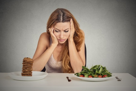 tired: Young woman tired of diet restrictions deciding whether to eat healthy food or sweet cookies she is craving sitting at table isolated grey background. Human face expression emotion. Nutrition concept Stock Photo