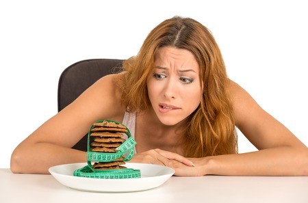 comida chatarra: Retrato joven mujer infeliz azúcar antojo galletas dulces, pero preocupado por el aumento de peso sentado en la mesa aislada en el fondo blanco. Emoción expresión humana. Concepto de la dieta nutricional dilema