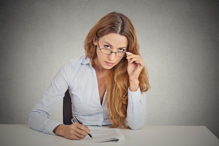 skeptic: Curious corporate businesswoman with glasses sitting at desk skeptically looking at you scrutinizing isolated on office grey wall background. Human face expression, body language, attitude, perception