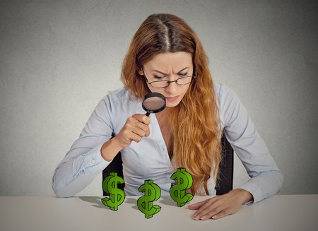multiply: penny pincher. Business woman looking through magnifying glass dollar signs symbol on table isolated grey wall office background. Economy financial wealth success concept. Ponzi scheme investigation
