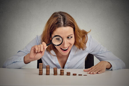 stingy: Closeup portrait excited greedy business woman wall street executive looking at growing stack of coins through magnifying glass isolated grey wall office background. Human face expression. Economy