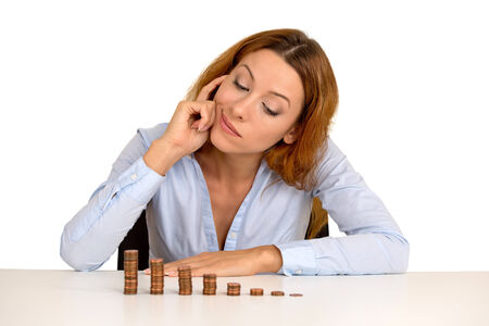pennies: Portrait thoughtful young business woman corporate executive sitting at table with growing stack of coins isolated on white background. Face expression. Financial economy banking savings concept Stock Photo