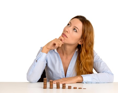 cashflow: Portrait thoughtful young business woman corporate executive sitting at table with growing stack of coins isolated on white background. Face expression. Financial economy banking savings concept Stock Photo