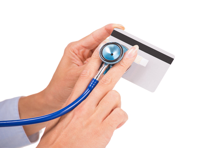 fraudulent: Woman hands holding listening credit card with stethoscope isolated on white background. Safety of online banking, fraudulent transaction, financial condition, cyber risk, self assessment concept. Stock Photo