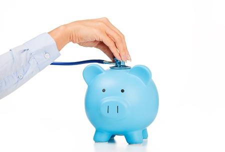 돼지 저금통 및 청진 흰색 배경에 고립입니다. 건강 관리 비용. 재무 상태 조건 자체 평가 개념. 의료 보험 비용에 대한 금융 시스템 점검 또는 절약 스톡 콘텐츠