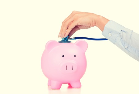surgery expenses: Piggy bank and stethoscope Isolated on white background. Health care cost. Financial state condition self assessment concept. Financial system checkup or saving for medical insurance costs