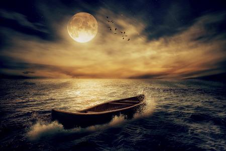 путешествие: Лодка отходит от прошлого в середине океана после шторма без курса по лунным небом ночном фоне горизонта облака. Концептуальная природа пейзаж заставка. Жизнь заставка будущей концепции надежды