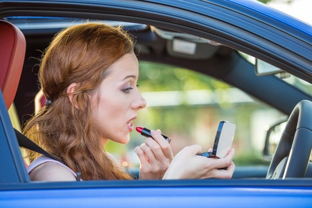 inexperienced: Young woman applying makeup while driving car Stock Photo