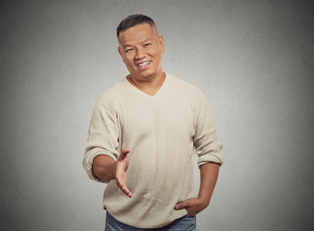 extending: Closeup portrait handsome young adult smiling man giving extending arm for handshake at camera gesture isolated grey wall background. Positive emotion facial expression feeling attitude perception Stock Photo