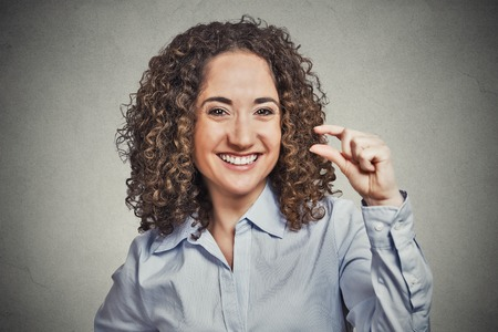 wee: Closeup portrait, funny young curly brown hair woman showing small amount gesture with hand fingers isolated grey background. Human emotion facial expression feelings, body language, signs, symbols Stock Photo