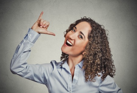 college dorm: Lets drink hand gesture. Portrait happy silly goofy woman gesturing showing with hand thumb to go out party get drunk isolated grey background. Positive human emotion face expression body language