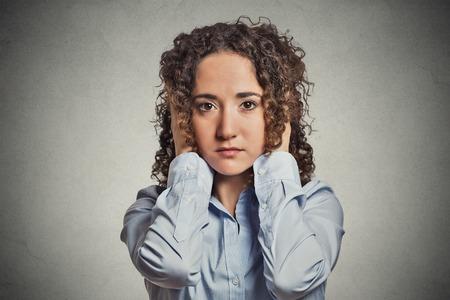 oido: Retrato del primer atractivo pac�fica relajado mirando Mujer joven que cubre sus o�dos ojos abiertos aislados fondo gris pared de la oficina. No escuchen el concepto de la idea del mal. La emoci�n humana actitud expresi�n facial