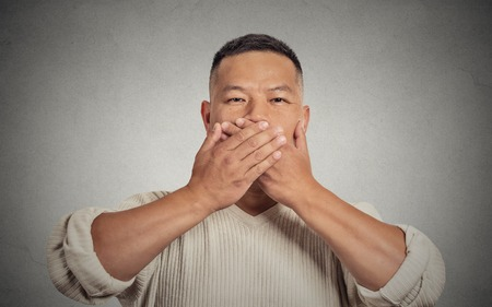 Closeup portrait headshot young man student worker employee covering his mouth with hands. Speak no evil concept isolated grey background. Human face expression feeling sign body language perception