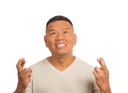 Closeup portrait anxious guy, middle aged man crossing fingers, wishing, hoping for best miracle isolated white background. Positive human emotion face expression feeling attitude anticipation
