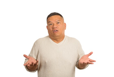 stupid body: Closeup portrait dumb clueless man arms out asking why whats problem who cares so what I dont know isolated white background. Negative human emotion face expression feeling body language reaction Stock Photo