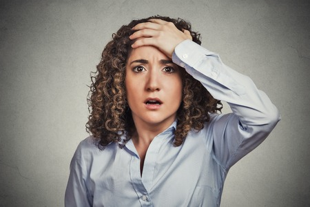 Closeup portrait headshot terrified young business woman looking shocked, surprised, full disbelief, hand on head isolated grey wall background. Negative emotion facial expression feeling reaction