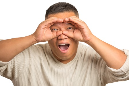 corporate espionage: Closeup portrait headshot surprised curious guy, funny man, looking through binoculars, searching something shocked by what is in future isolated white background. Human face expression emotion