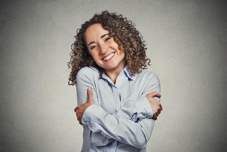 Close-up portret vertrouwen lachende vrouw met knuffelen zichzelf geïsoleerde grijze muur achtergrond. Positieve menselijke emotie, gezichtsuitdrukking, gevoel, reactie, situatie, houding. Hou van jezelf begrip