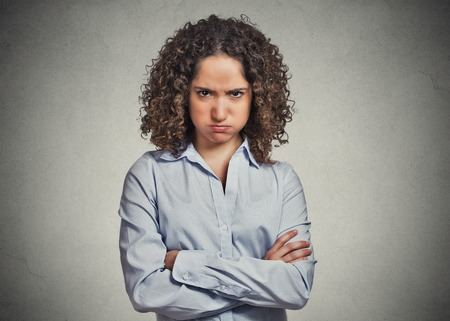 Closeup portrait of angry young woman puffing cheeks isolated on grey wall background. Negative human emotions face expressions feelings perception Standard-Bild