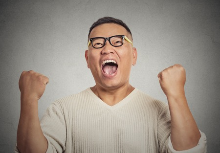 enrolled: Closeup portrait successful student with glasses man winning, fists pumped celebrating success isolated grey wall background. Positive human emotion face expression. Life perception achievement vision