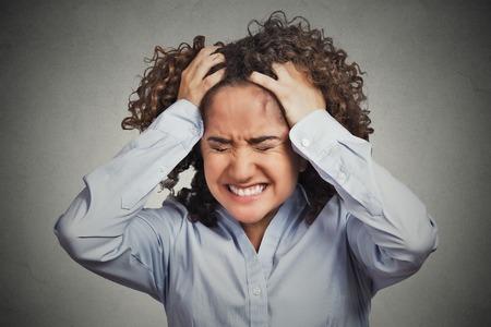 languages: Frustrado mujer joven tensionada. Headshot infeliz niña abrumada tiene dolor de cabeza mal día saca su pelo aislado en el fondo gris de la pared. La emoción negativa sentimientos expresión cara percepción Foto de archivo