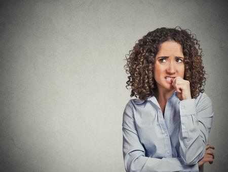Close-up portret nerveus ogende vrouw haar nagels bijten verlangen iets angstig geïsoleerde grijze muur achtergrond met een kopie ruimte. Negatieve menselijke emotie lichaamstaal perceptie gezichtsuitdrukking