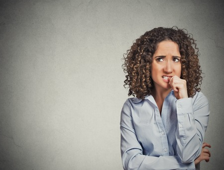 embarrassed: Closeup portrait nervous looking woman biting her fingernails craving something anxious isolated grey wall background with copy space. Negative human emotion facial expression body language perception Stock Photo