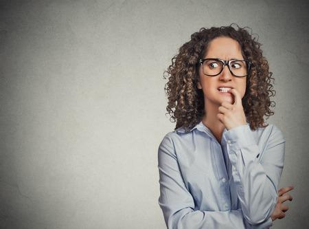 conflictos sociales: Retrato del primer mujer nerviosa con gafas mordiendo sus u�as antojo de algo, aislado ansioso fondo gris de la pared con copia espacio. Las emociones humanas negativas, la expresi�n facial lenguaje corporal