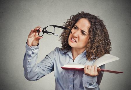 lentes de contacto: Primer retrato joven, la mujer no puede ver leyó el libro tiene problemas de visión gafas equivocadas prescritos aislado molesto fondo de la pared gris. Expresión facial emoción humana, la reacción tema sintiendo salud