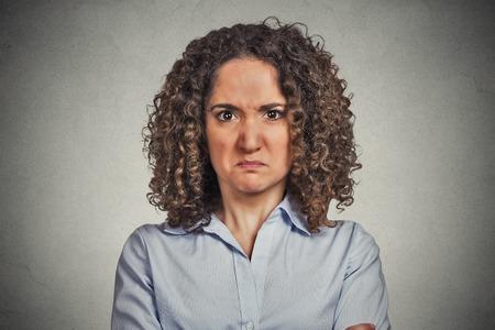 headshot boze vrouw die op grijze muur achtergrond. Negatieve gezichtsuitdrukking lichaamstaal