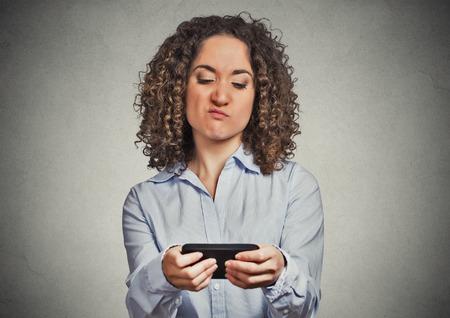 mujer decepcionada: Retrato joven mujer enojada infeliz, molesto por algo, alguien en su tel�fono celular, mientras que los mensajes de texto, recibir aislado mal mensaje de texto sms fondo de la pared gris. Rostro humano reacci�n emoci�n expresi�n Foto de archivo