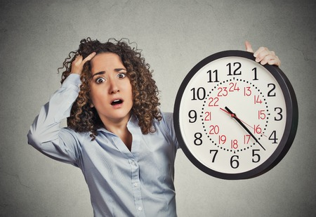 failed plan: Time pressure. Closeup portrait woman stressed corporate employee holding clock looking anxiously running out of time isolated grey wall background. Human face expression emotion reaction. Last moment