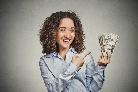 savings goals: Closeup portrait super happy excited successful young business woman holding money dollar bills in hand isolated on grey wall background. Positive emotion facial expression feeling. Financial reward