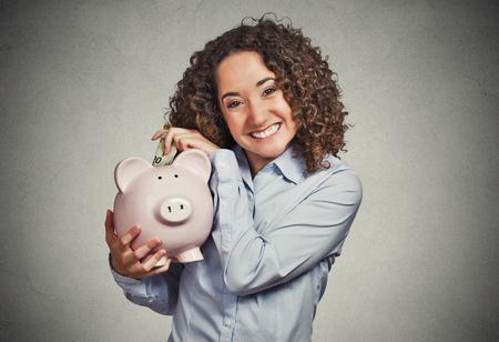 cuenta bancaria: Primer retrato feliz sonriente empleado del banco mujer de negocios, estudiante de la celebración hucha, contentos de abrir una cuenta de ahorros aislado fondo gris. Concepto financiero. Expresión facial emoción positiva