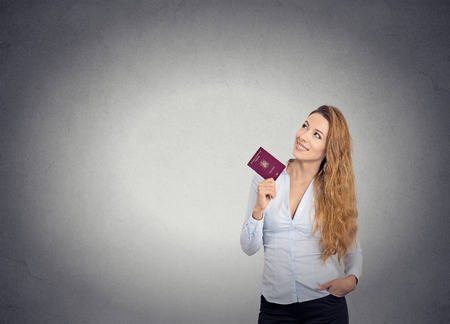 overseas visa: Attractive smiling happy woman standing holding passport looking up imagining new pleasant future life isolated on grey wall background with copy space. Positive facial expression, body language