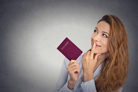 Attractive smiling happy woman standing holding passport looking up imagining new pleasant future life isolated on grey wall background with copy space. Positive facial expression, body language