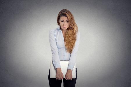 lenguaje corporal: La falta de confianza. Inseguro portátil mujer que sostiene joven preocupante que se siente aislado torpe fondo de la pared gris. Expresión de la cara humana percepción vida lenguaje corporal emoción