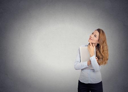 Portret gelukkig mooie vrouw met laptop denken opzoeken van geïsoleerde grijze muur achtergrond met een kopie ruimte. Positieve menselijk gezicht uitdrukkingen, emoties, gevoelens, lichaamstaal, perceptie