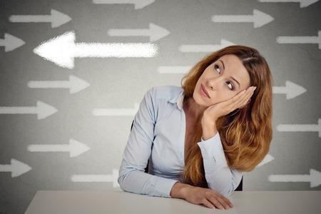 思慮深い女性は流れに対して行くチャンスを撮影します。灰色の壁オフィス背景に分離のテーブルに座って思慮深い実業家。相殺の概念。表情、感