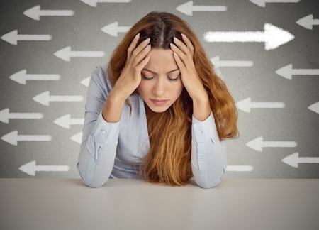 Thoughtful woman taking a chance going against flow. Thoughtful businesswoman sitting at table isolated on grey wall office background. Counterbalance concept. Face expression, emotion, intuition