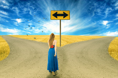 fork in the road: Young woman standing in front of two roads