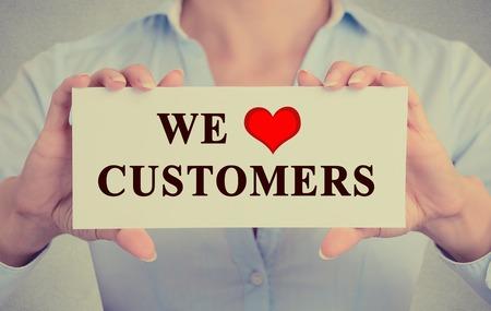 Close-up retro beeld zakenvrouw handen die witte bord of kaart met een boodschap die we liefhebben klanten die op grijze kantoor muur achtergrond