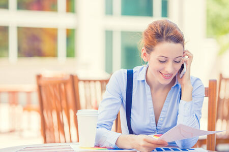 reviewing documents: Portrait young professional woman talking on mobile phone reviewing documents papers outside corporate office isolated city building background. Positive face expression emotion, life success concept Stock Photo