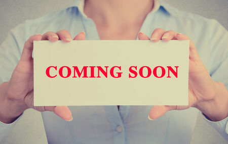 relaunch: Businesswoman hands holding white card sign with coming soon text message isolated on grey wall office background.
