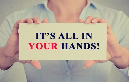 Image of businesswoman hands holding white card with Its All in Your hands! Motivating message sign isolated on grey wall office background.