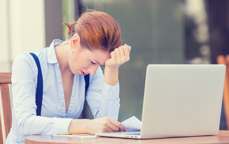 frustrated student: Portrait young stressed displeased worried business woman sitting in front of laptop computer isolated outdoors city building background. Negative face expression emotion feelings problem perception Stock Photo