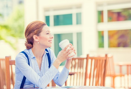 business mind: Side profile portrait young smiling woman drinking coffee outside corporate office isolated city building background coffee shop. Positive human face expression, emotion, life success, leisure concept Stock Photo