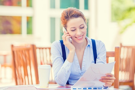 insurance consultant: Portrait young professional woman talking on mobile phone reviewing documents papers outside corporate office isolated city building background. Positive face expression emotion, life success concept Stock Photo