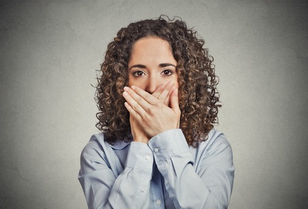 closed mouth: Closeup portrait young woman covering closed mouth with hands. Speak no evil concept isolated grey wall background. Human emotion face expression sign symbol. Media news employee relationship coverup